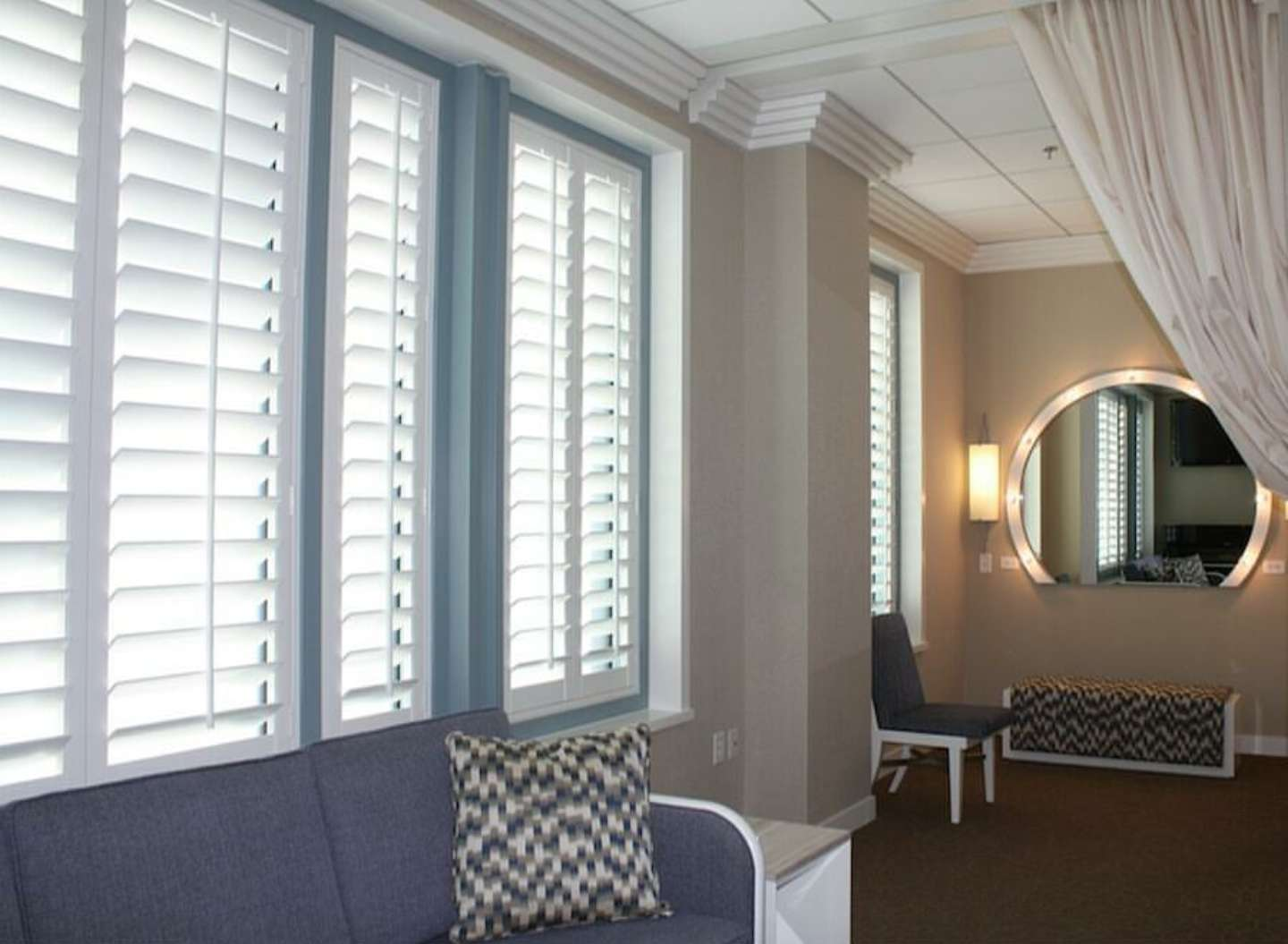 Plantation shutters in hallway with circular mirror